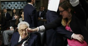 Alli McCracken, a peace activist with CODEPINK, shows former Secretary of State Henry Kissinger a pair of handcuffs during a protest at a Senate hearing on Thursday. If there was justice in this world, argue human rights activist, Kissinger would be in prison for his role in perpetrating war crimes as opposed to sitting before the Senate Armed Services Committee to offer his assessment of world affairs. (Photo: Courtesy of CODEPINK)