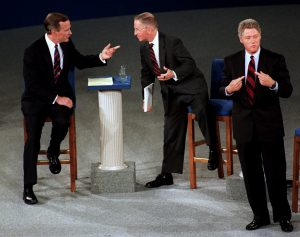 FILE - In this Oct. 15, 1992 file photo, President Bush, left, talks with independent candidate Ross Perot as Democratic candidate Bill Clinton stands aside at the end of their second presidential debate in Richmond, Va.   (AP Photo/Marcy Nighswander, File)