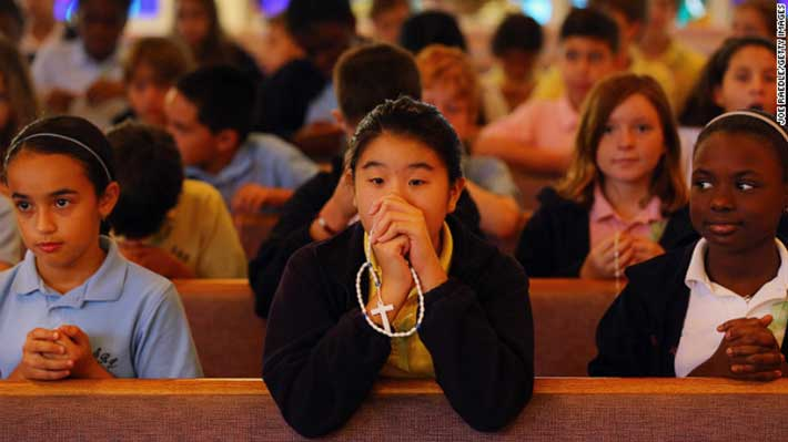 Students participate in a prayer service for victims of the Newtown, Connecticut, mass shooting at St. Rose of Lima School in Miami on Friday, December 21. (Joe Raedle / Getty Images)